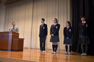 ベトナムに派遣される中等部3年生4人 (左から 関令法君、渡辺咲弥さん、原田佳子さん、内川亜美さん) と引率の小見山先生を、始業式の後、紹介しました